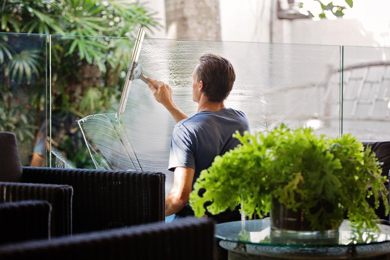 Mann beim Fensterputzen